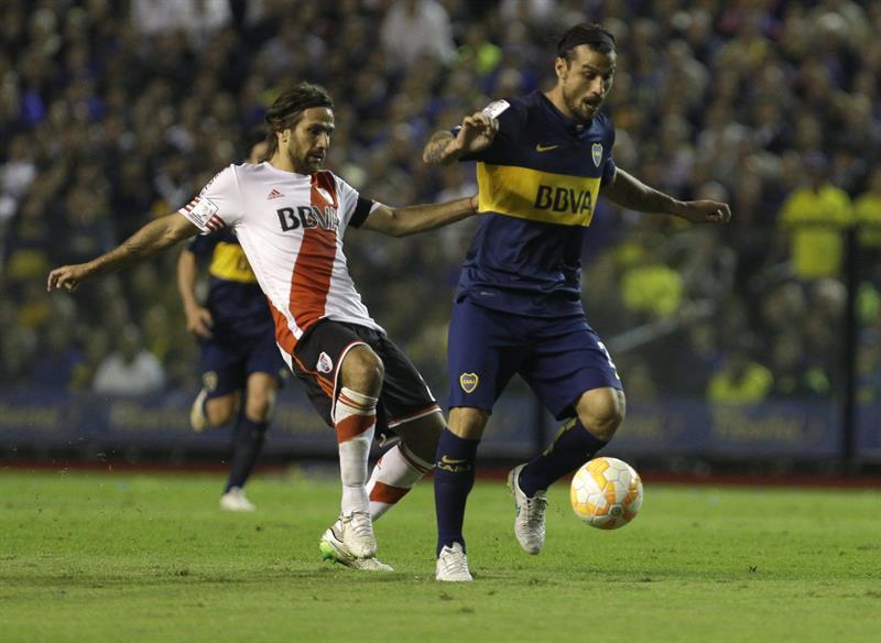 El jugador Daniel Osvaldo (d) de Boca Juniors disputa el balón con Leonardo Ponzio (i) de River Plate. Foto: EFE