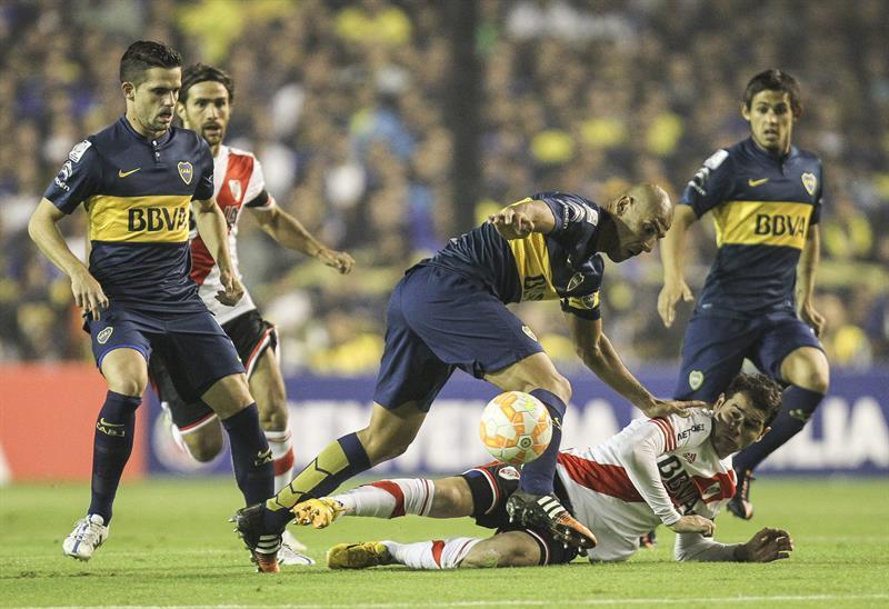 El jugador Daniel Díaz (c-arriba) de Boca Juniors disputa el balón con Gonzalo Martínez (abajo) de River Plate. Foto: EFE