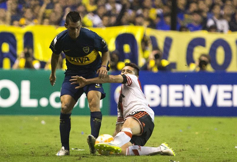 Cristian Pavón (i) de Boca Juniors disputa el balón con Matías Kranevitter de River Plate. EFE