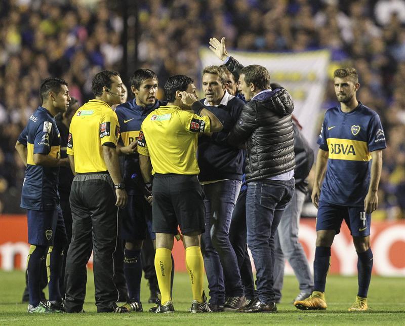 El entrenador Adolfo Arruabarrena (d) de Boca Juniors habla con los árbitros luego de que lanzaran gas pimienta desde la tribuna. Foto: EFE