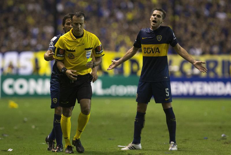 Fernando Gago de Boca Juniors reclama una falta al árbitro Darío Herrera. EFE