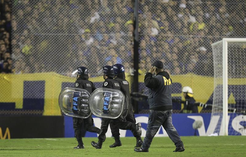 Miembros de la Policía Federal Argentina (PFA) entran a la cancha luego de que lanzaran gas pimienta. Foto: EFE