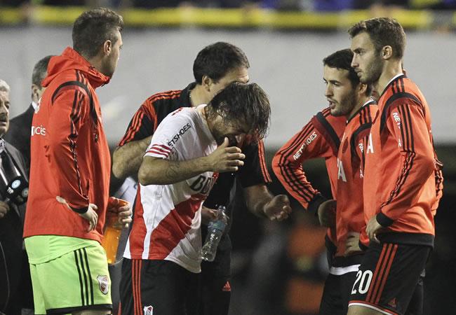 Leonardo Ponzio de River Plate se limpia el rostro luego de que lanzaran gas pimienta desde la tribuna. Foto: EFE