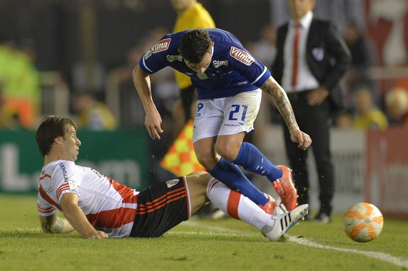 Eugenio Mena (d) del Cruzeiro disputa el balón con Fernando Cavenaghi (i) de River. Foto: EFE