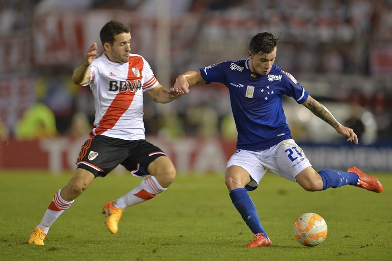 Eugenio Mena (d) del Cruzeiro disputa el balón con Camilo Mayada (i) de River. Foto: EFE