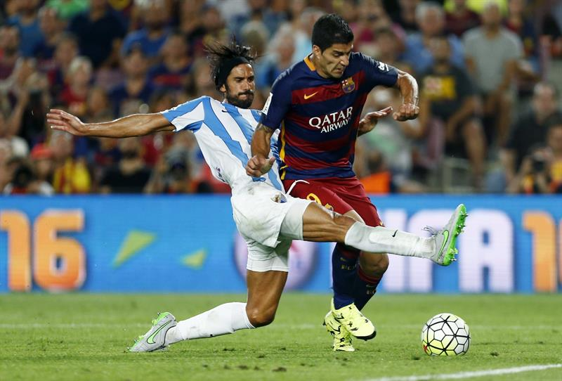 El defensa argentino del Málaga CF Marcos Angeleri (i) lucha el balón con el delantero uruguayo Luis Suárez, del FC Barcelona. EFE