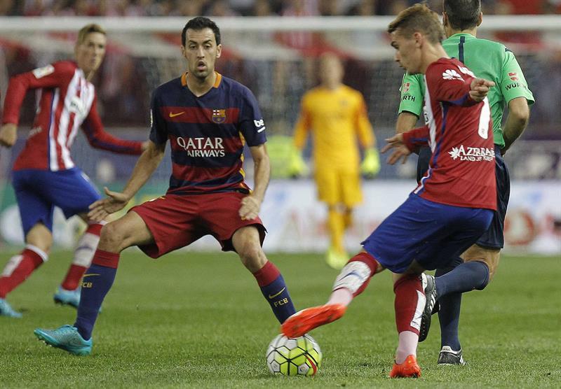 El delantero del Atlético de Madrid, Antoine Griezmann (d), disputa un balón con el centrocampista del FC Barcelona, Sergio Busquets. Foto: EFE