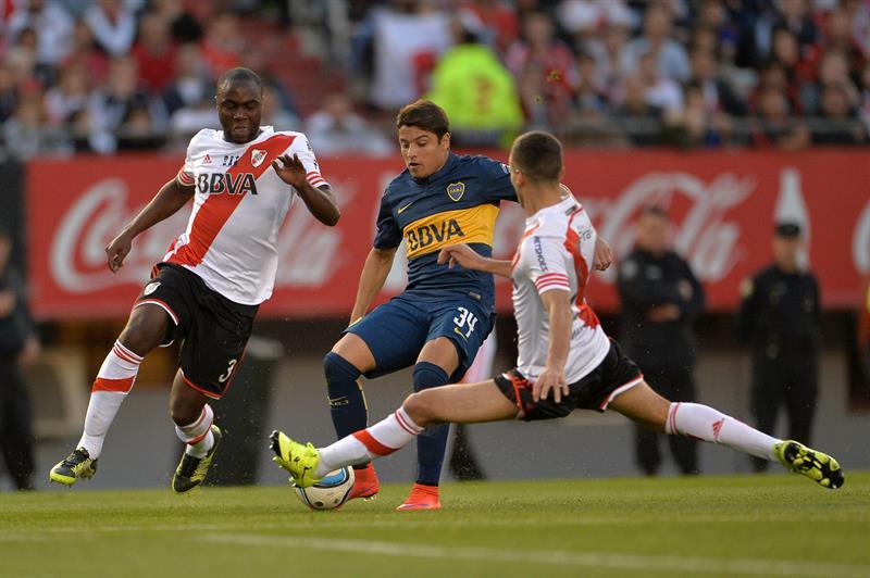 El jugador de Boca Juniors Sebastian Palacios (c) disputa la pelota con Emanuel Mammana (i) de River Plate. EFE