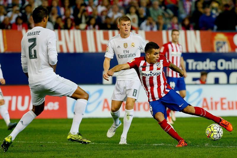 El delantero argentino del At. de Madrid, Ángel Correa (d), golpea el balón ante el defensa francés del Real Madrid. EFE