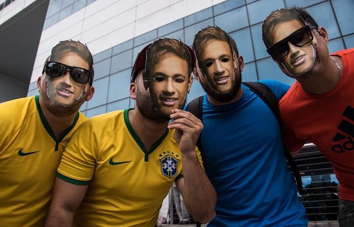 Hinchas usaron máscaras de Neymar fuera del hospital donde fue operado. (AFP). Foto: AFP