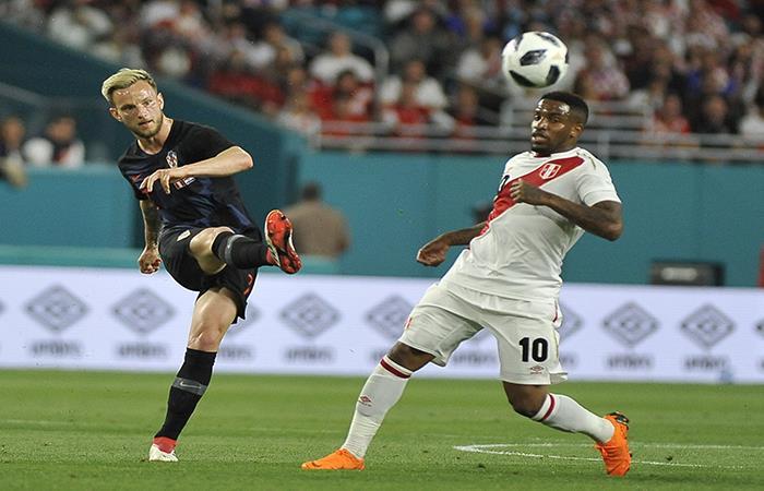 Iván Rakitic disputando un balón con Jefferson Farfán. (AFP)