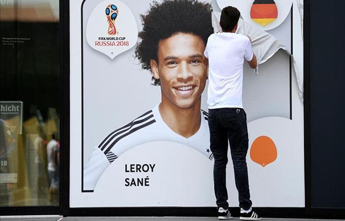 Un empleado saca el poster de Leroy Sané colgado en la fachada de la Federación Alemana. Foto: AFP
