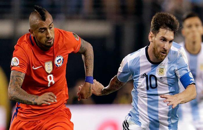 Arturo Vidal disputa un balón con Lionel Messi. (FOTO: AFP)