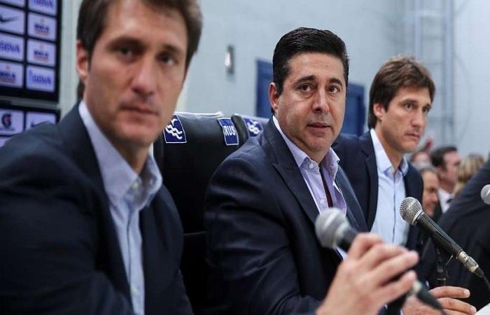 Daniel Angelici junto a los Barros Schelotto. Foto: EFE